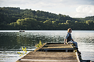 Germany, Rhineland-Palatinate, Laach Lake, Man sitting on wooden boardwalk - PAF000912