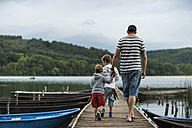 Germany, Rhineland-Palatinate, Laacher See, father walking with two sons on jetty - PAF000920