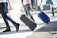 Friends on city trip with rolling suitcases - ZEF000779