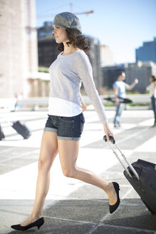 Walking young woman with rolling suitcase - ZEF000782