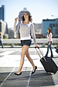 Walking young woman with rolling suitcase - ZEF000783