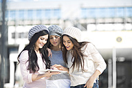 Three female friends with wool caps using digital tablet - ZEF000795