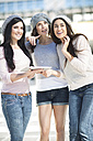 Three female friends with wool caps and digital tablet - ZEF000796