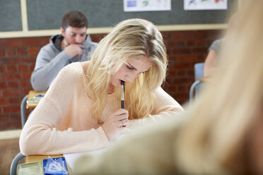 Female student in classroom writing at desk - ZEF000741