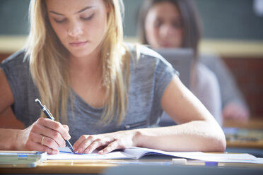 Female student in classroom writing at desk - ZEF000685