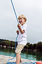 Portrait of smiling little boy standing on a jetty pulling a rope - DAWF000115