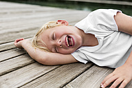 Portrait of laughing little boy lying on a jetty - DAWF000125