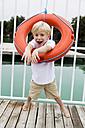 Portrait of little boy looking through a lifesaver - DAWF000144