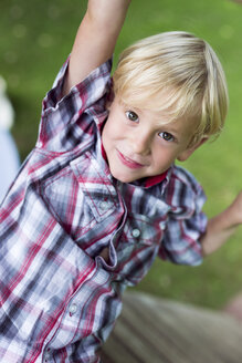 Portrait of smiling little boy climbing on playground equipment - DAWF000148