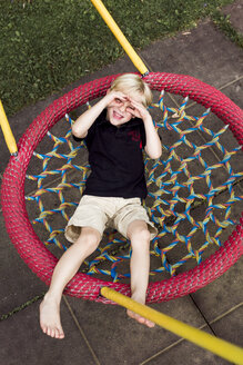 Portrait of little boy relaxing on playground equipment shielding his eyes with his hands - DAWF000139