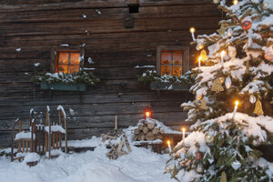 Austria, Salzburg State, Altenmarkt-Zauchensee, facade of wooden cabin with lightened Christmas Tree in the foreground - HHF004862