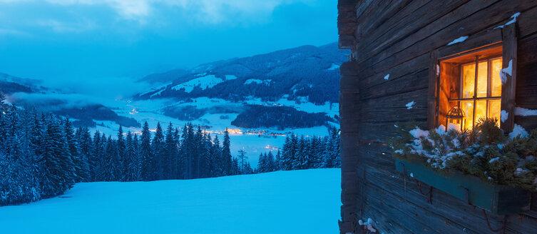 Austria, Salzburg State, Altenmarkt-Zauchensee, facade of wooden cabin with lightened window in winter - HHF004866