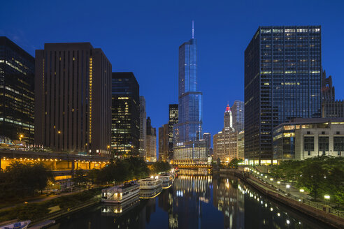 USA, Illinois, Chicago, High-rise buildings, Trump Tower at Chicago River in the evening - FOF006986
