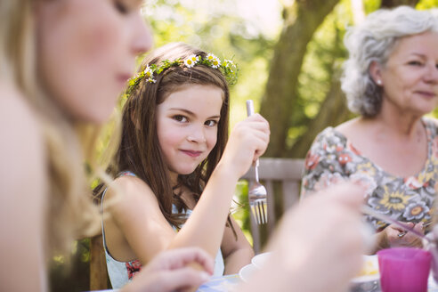Grl sitting between mother and grandmother at a garden table - MFF001252