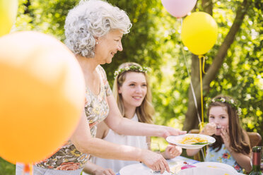 Grandmother serving daughter and granddaughter pasta on a garden party - MFF001258