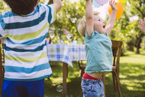 Children trying to catch soap bubbles in garden - MFF001293