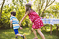 Boy and girl playing tag in garden - MFF001278