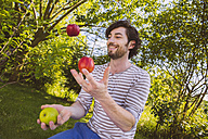 Man juggling with fruit in garden - MFF001298