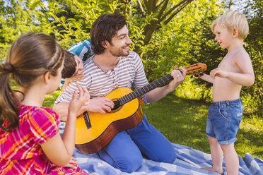 Father with children playing guitar in garden - MFF001303