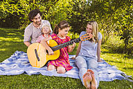 Family on picnic blanket playing guitar - MFF001305