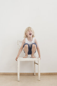 Portrait of screaming little boy crounching on a chair - MJF001331