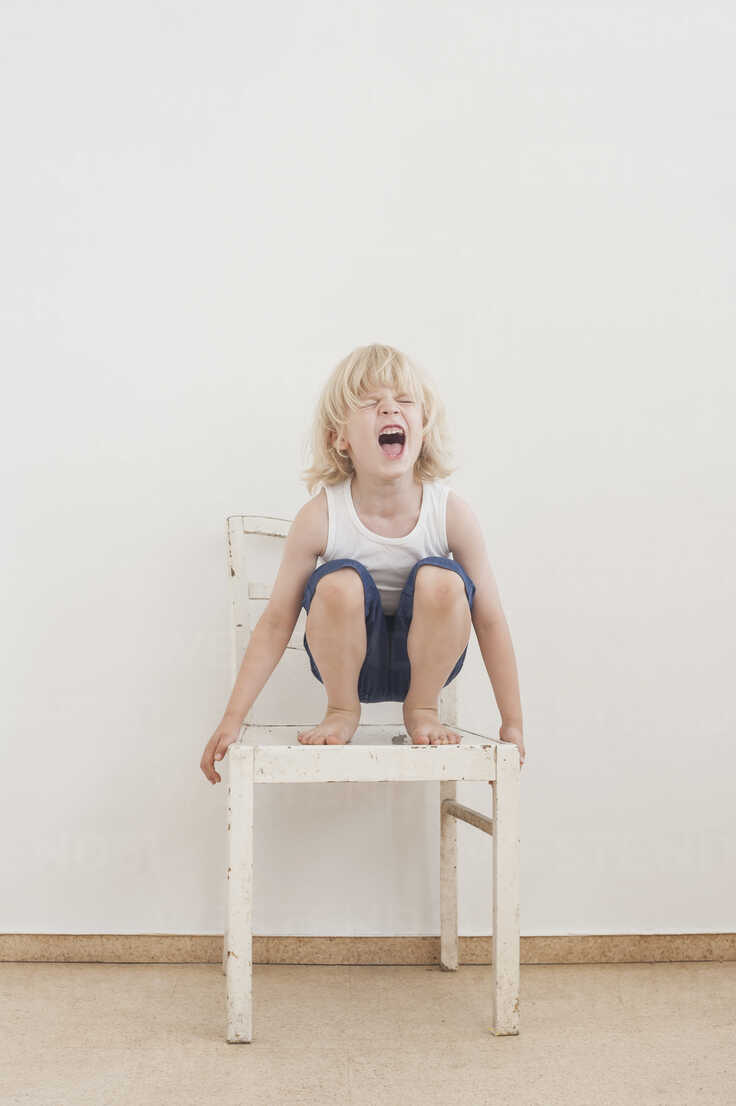 Portrait of screaming little boy crounching on a chair - MJF001331 - Jana Mänz/Westend61