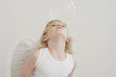 Portrait of little boy with angel wings blowing a soap bubble - MJF001344