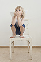 Portrait of little boy with angle wings crouching on a chair - MJF001348