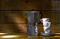 Espresso can and stack of three espresso cups in front of wooden wall - KSWF001330