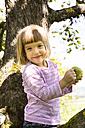 Portrait of smiling little girl sitting on an apple tree with bitten apple - LVF001793