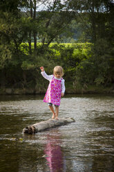 Little girl balancing on a rock in a river - LVF001802