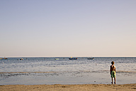Italy, Gorizia, Grado, boy standing at seafront looking at horizon - LVF001807