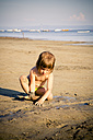 Italy, Gorizia, Grado, little girl playing on sandy beach - LVF001809