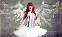 Portrait of woman with red hair and ballerina dress standing in front of wall with angle wings graffiti - AFF000150