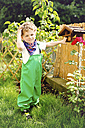 Portrait of little boy wearing green dungarees standing in the garden - AFF000084