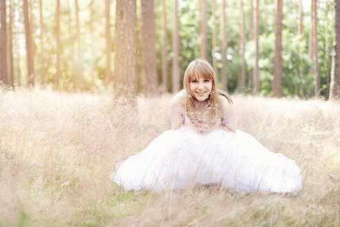 Happy bride wearing white wedding dress sitting on a meadow - AFF000074