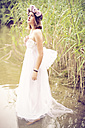 Woman wearing wedding dress and flower crown standing in the water - AF000146