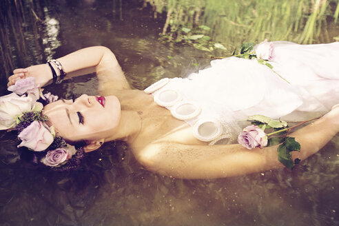 Portrait of young woman wearing wedding dress and flower crown lying in the water with closed eyes - AF000147