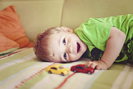 Portrait of happy little boy  lying on the couch - AFF000078