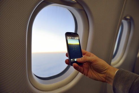 Man taking picture with smartphone at airplane window - BR000719
