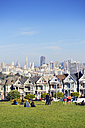 USA, California, San Francisco, Victorian houses at Alamo Square in front of the skyline - BR000689