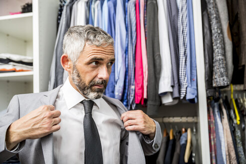 Businessman dressing at his walk-in closet - MBEF001191