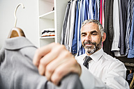 Portrait of businessman choosing jacket at his walk-in closet - MBEF001193