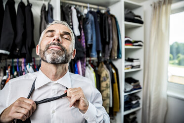 Businessman binding tie at his walk-in closet - MBEF001195