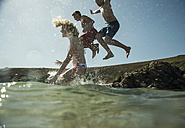 Three teenagers jumping into the sea - UUF001681