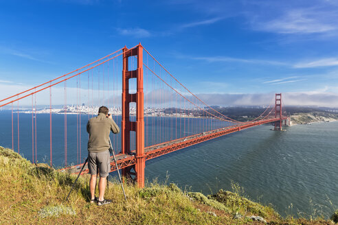 USA, California, San Francisco, man taking picture from skyline and Golden Gate Bridge - FOF007025