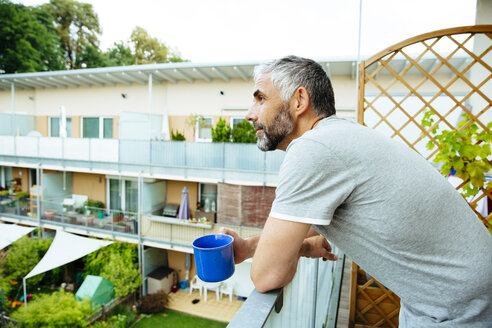 Man relaxing with cup of coffee on his balcony - MBEF001112