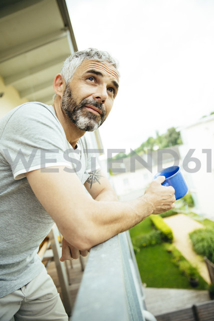 Portrait of man relaxing with cup of coffee on his balcony - MBEF001115 - Martin Benik/Westend61