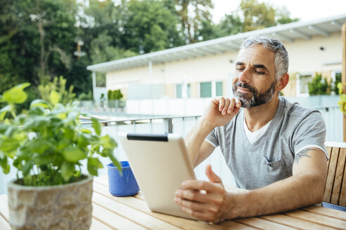 Portrait of man sitting on his balcony using digital tablet - MBEF001226