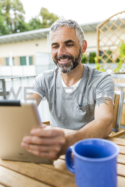 Portrait of smiling man sitting on his balcony using digital tablet - MBEF001121 - Martin Benik/Westend61